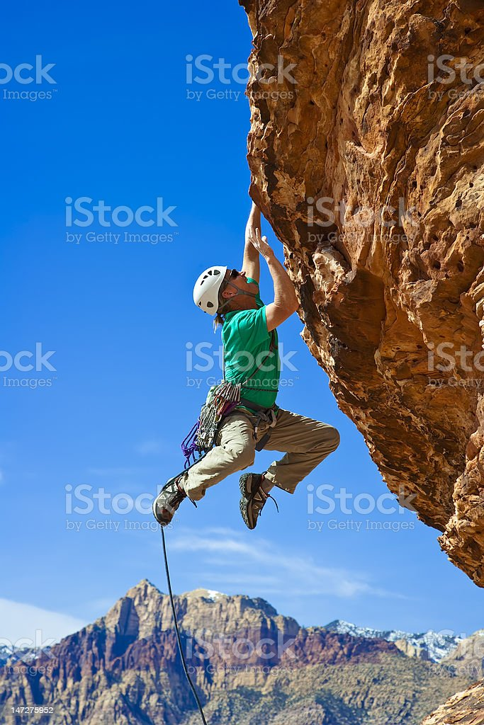 Male rock climber reaching for the summit. stock photo