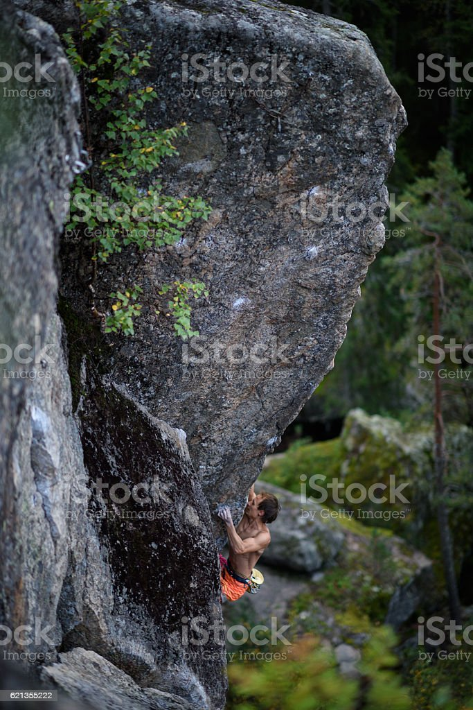 Male rock climber struggles to climb a challenging overhanging. stock photo