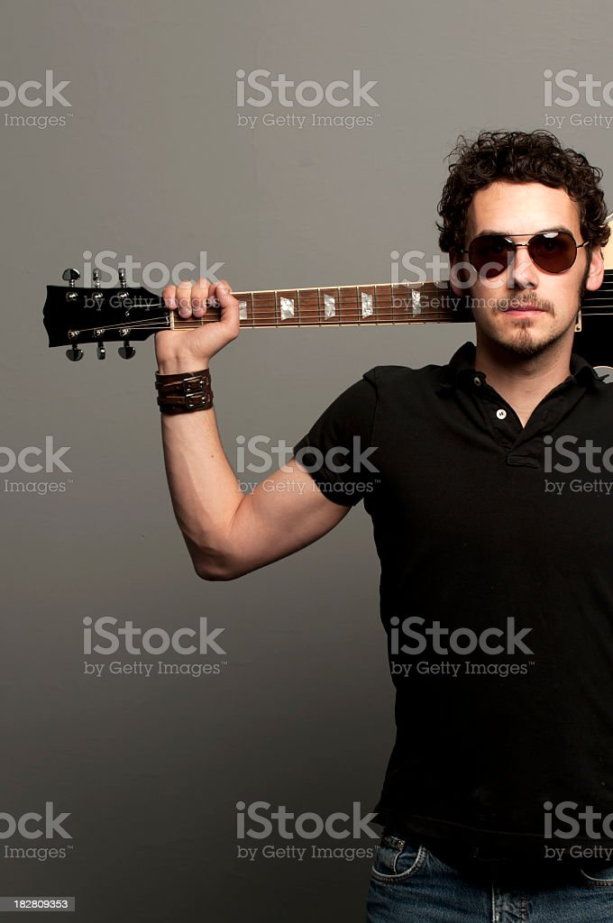 Male rockstar wearing black, holding guitar behind his head stock photo