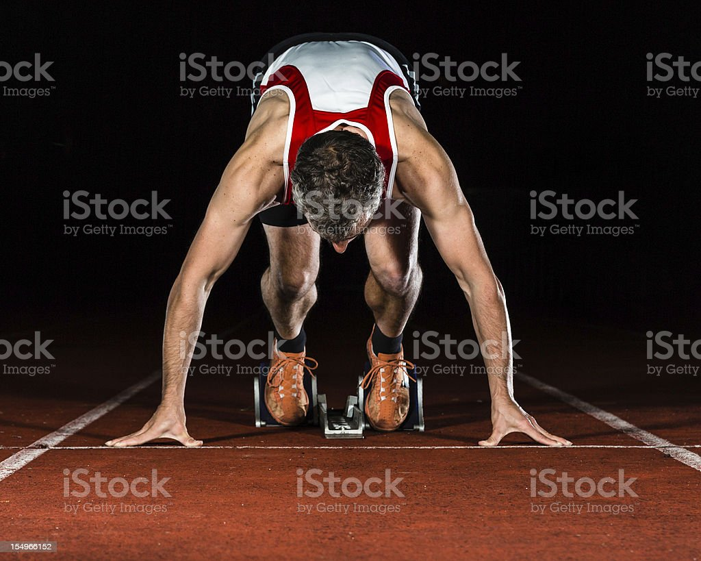 Male runner bent over in a sprint starting position on track stock photo