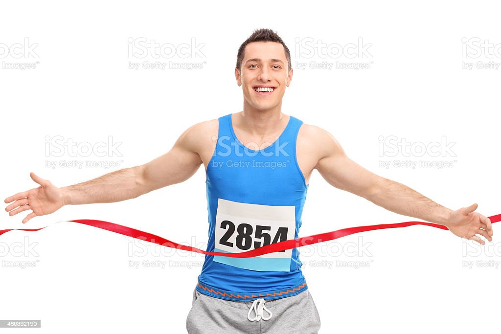 Male runner crossing the finish line stock photo