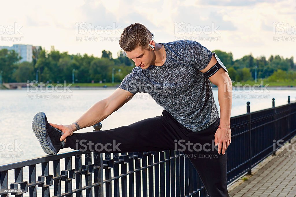Male runner doing stretching exercise stock photo