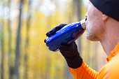 Male runner drining from vacuum flask