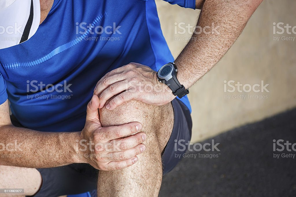 Male runner having problems in knee joint. stock photo