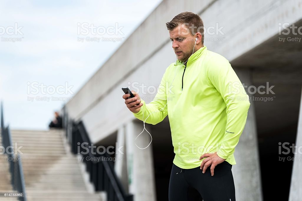 male runner in bright t-shirt using mobile phone stock photo