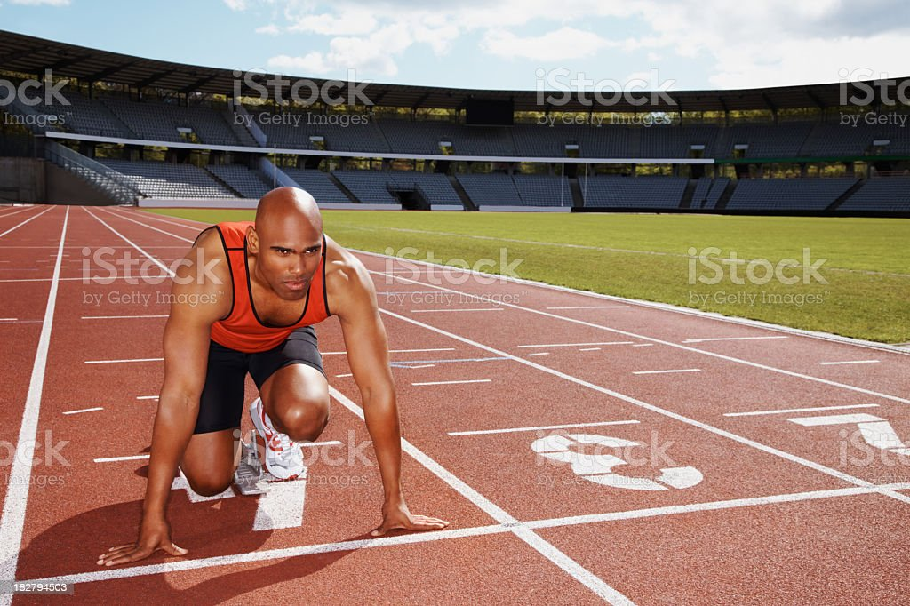 A male runner is squatted in the start position on a track royalty-free stock photo
