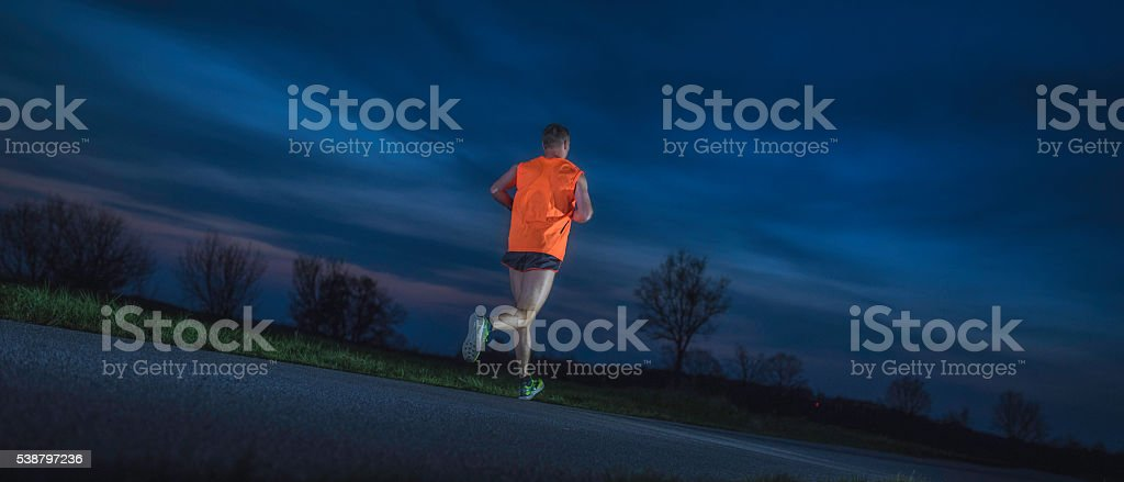 Male runner on the road in the evening stock photo