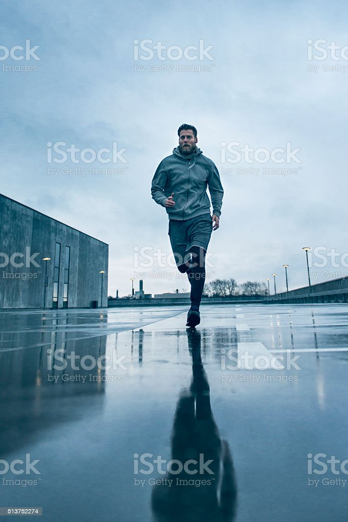 Male runner out for a fast run in the rain stock photo