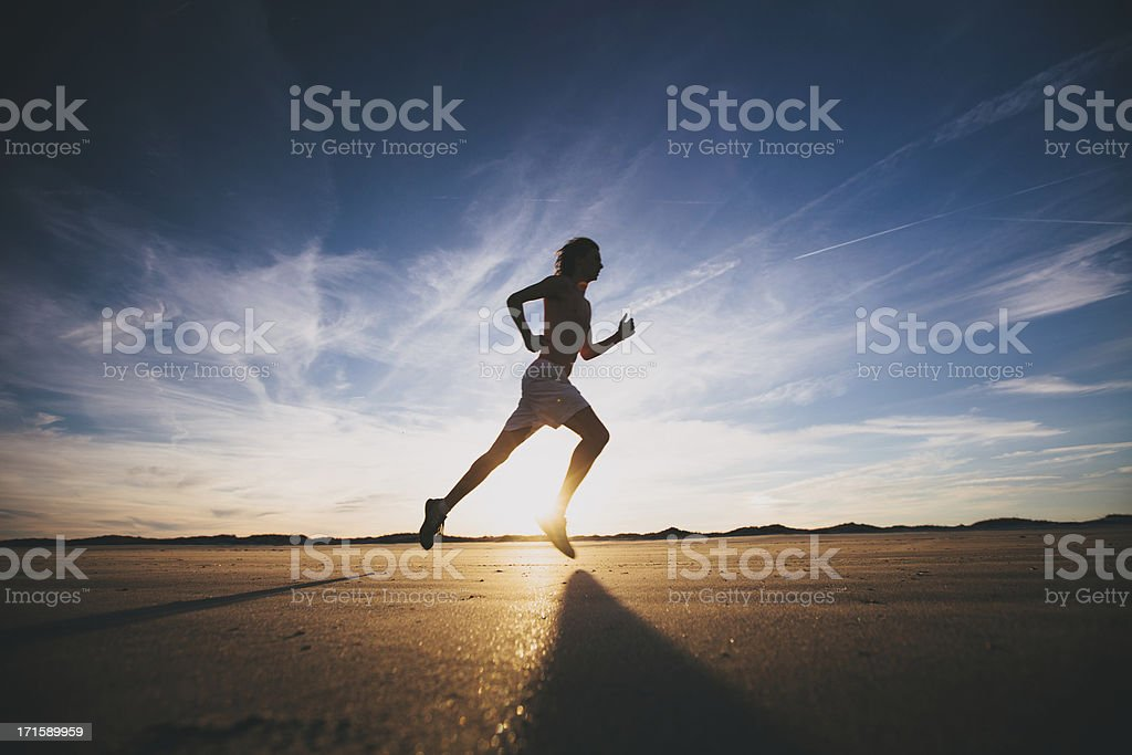 Male runner out for a training run at sunset stock photo