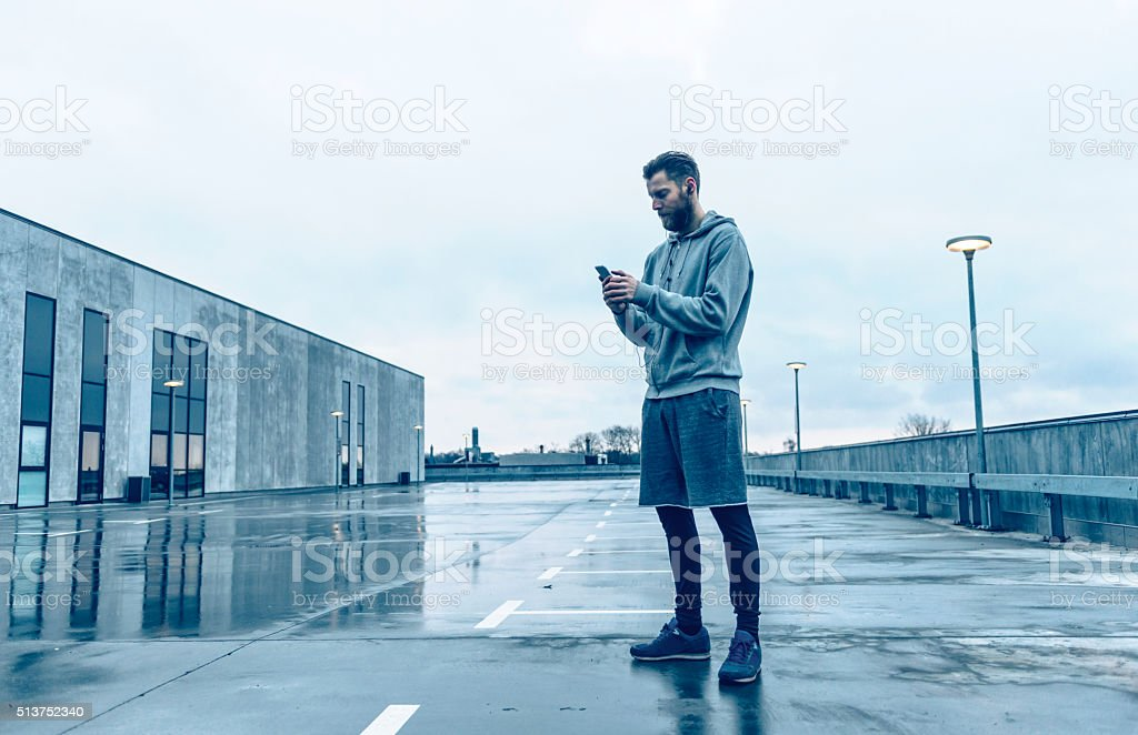Male runner plays with smart phone before run stock photo
