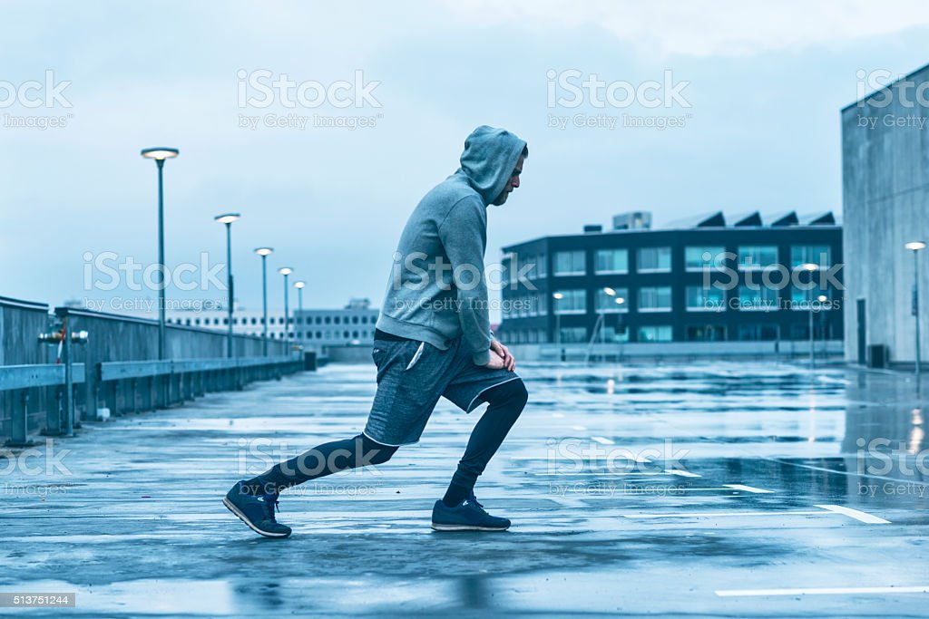 Male runner prepares for run and stretches leg stock photo