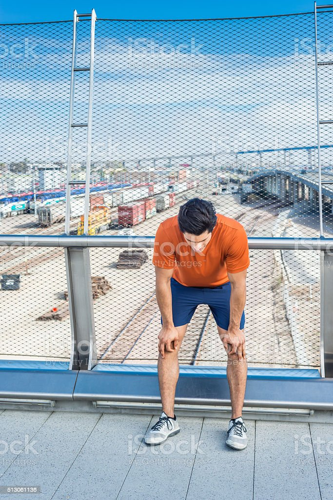 Male Runner Resting On A Bridge In San Diego stock photo