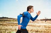 Male runner running in front of rural scene