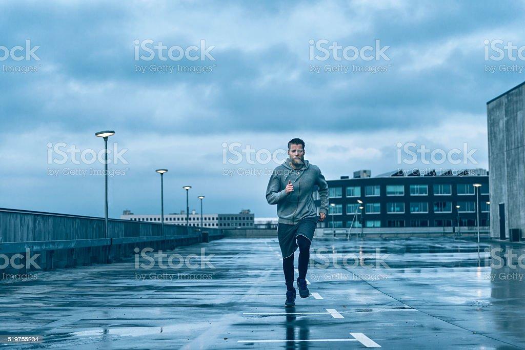 Male runner runs on wet streets after rain stock photo