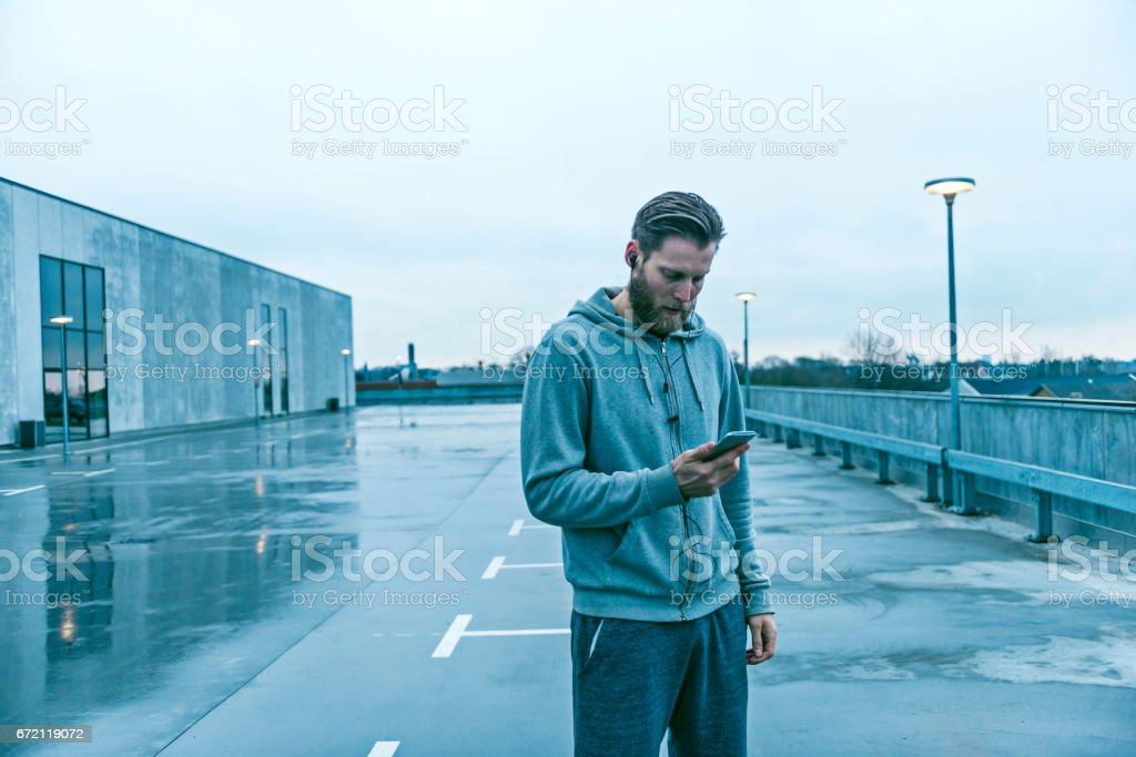 Male runner stands outside with mobile phone and headset stock photo
