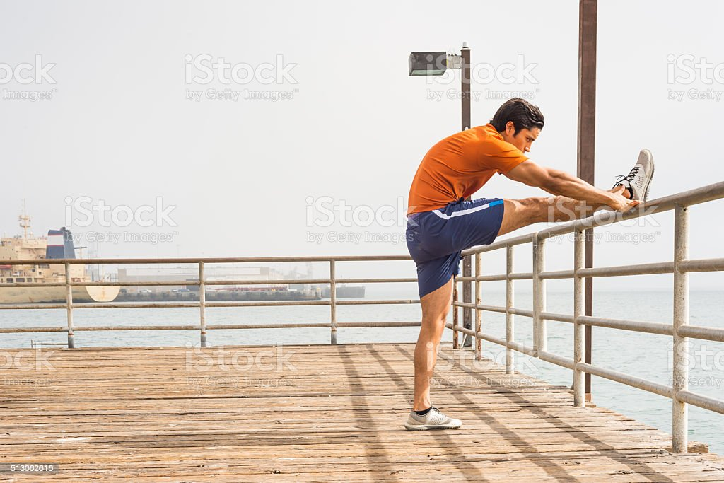 Male Runner Stretching On An Ocean Pier stock photo