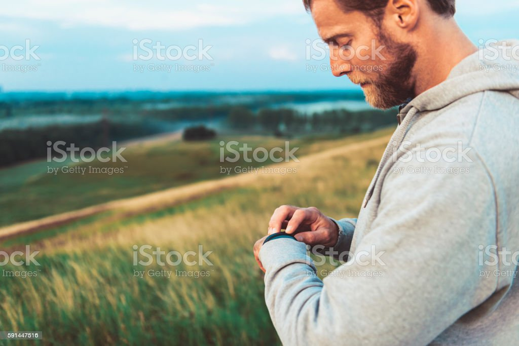 Male runner tracks fitness and activity with wristband stock photo