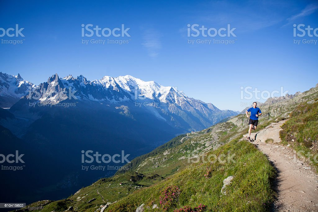 Male running along a mountain trail stock photo