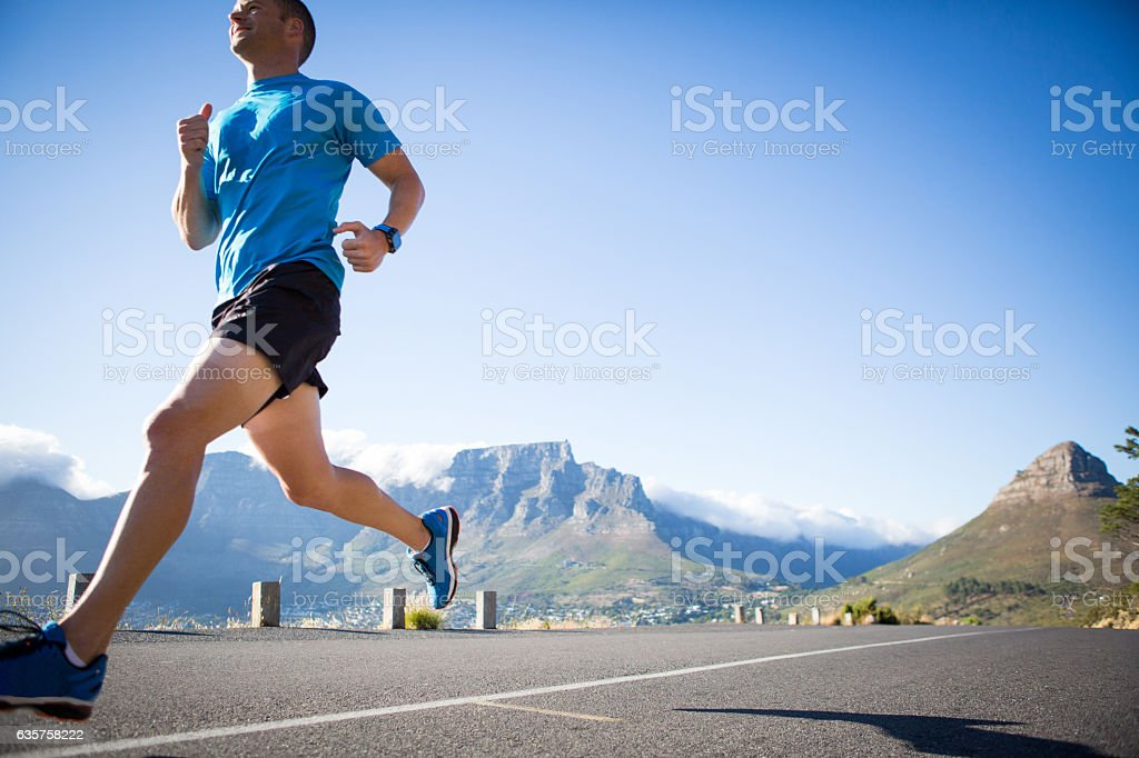 Male running fast on the road in the morning stock photo