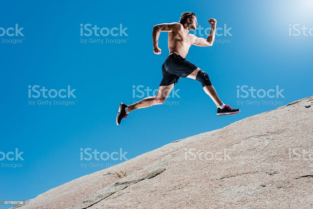 Male Running Up A Granite Boulder In The Mountains stock photo
