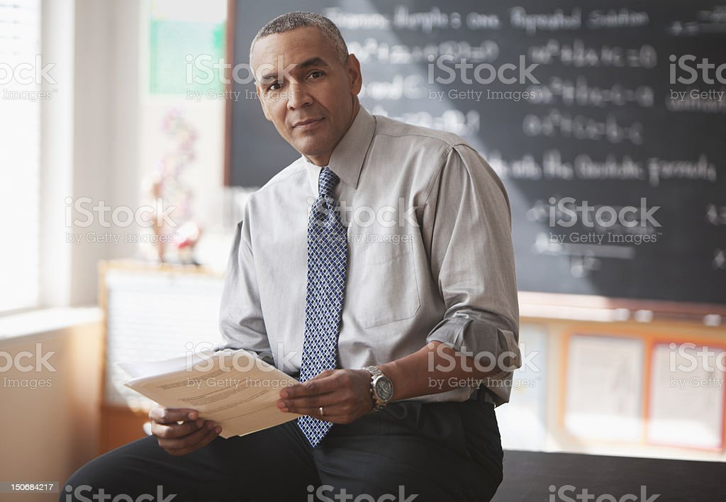 Male school teacher in front of blackboard with papers stock photo