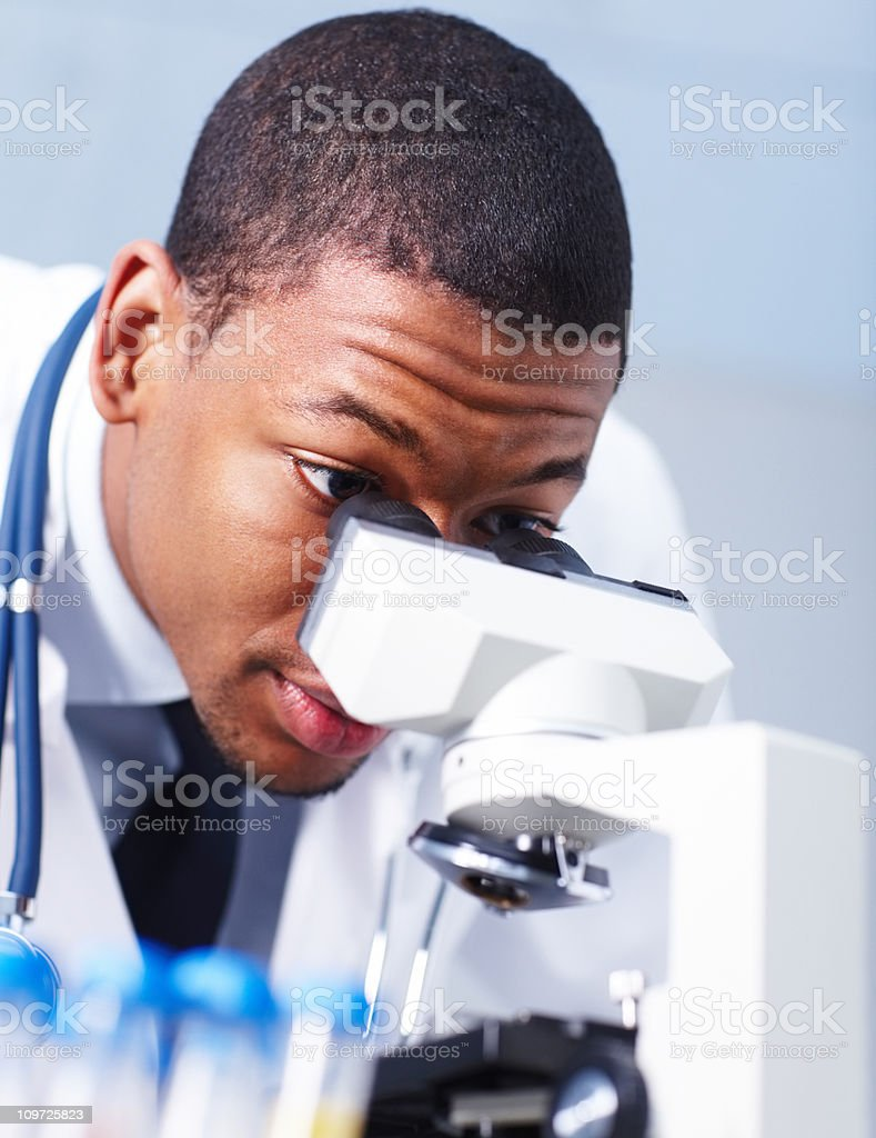 Male scientist looking through a microscope stock photo