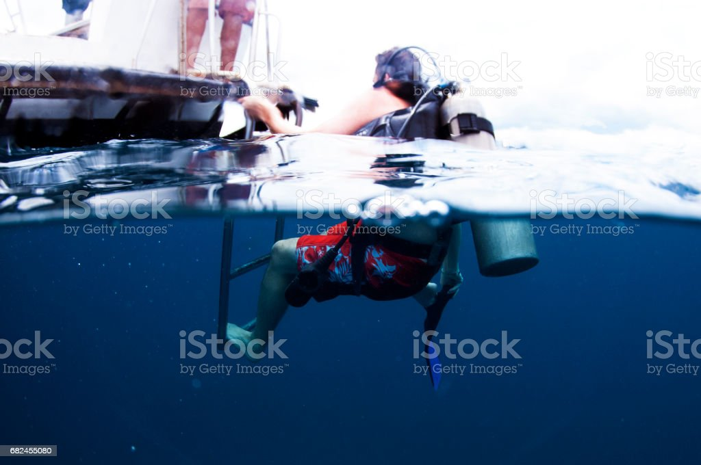 Male Scuba Diver at back of boat taking off fins to get back into boat above and below water camera climbing onto ladder stock photo