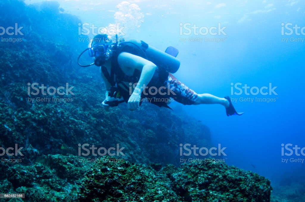 male scuba diver looking at camera over rocky area with bubbles stock photo