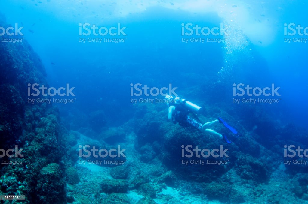 male scuba diver over rocky bottom in dark part of the ocean stock photo