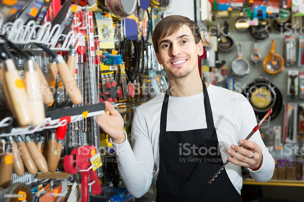 male seller posing at tooling section of household store stock photo