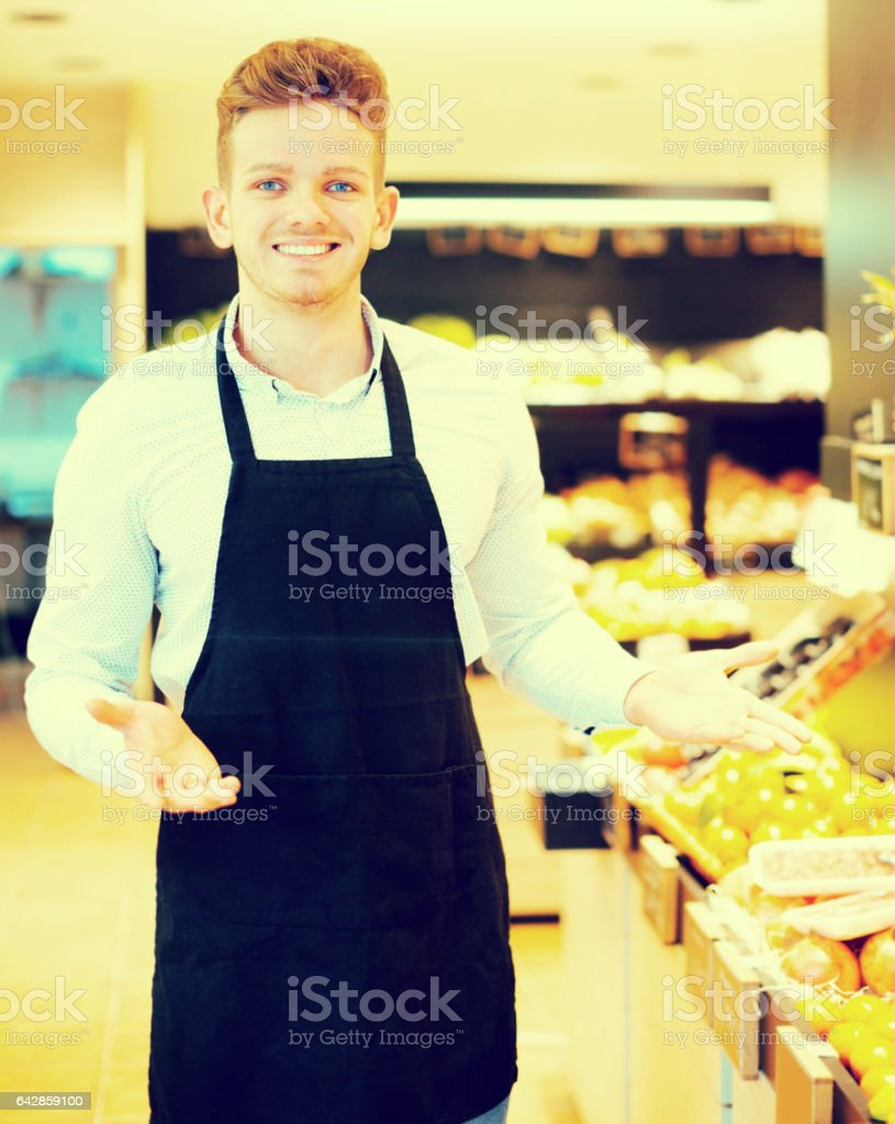 Male seller showing assortment of grocery shop stock photo