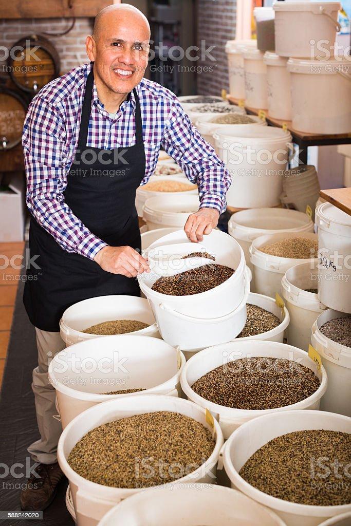 male seller taking bird seeds stock photo