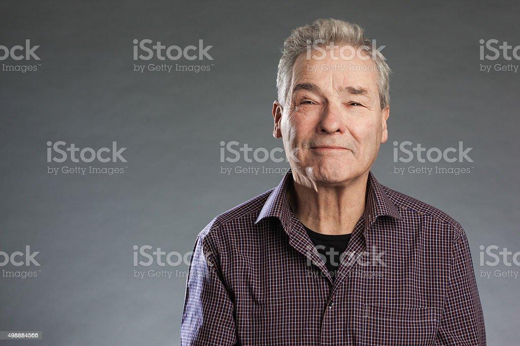 Male senior looking happily into camera. Horizontal portrait on stock photo