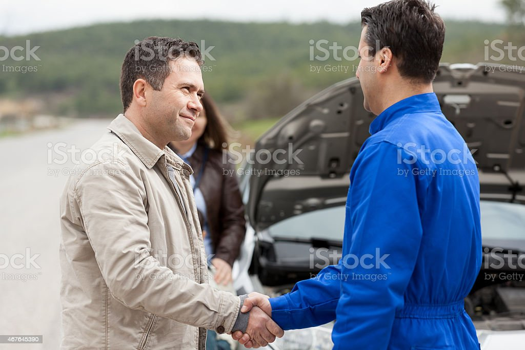 Male Shaking Hands With Car Mechanic stock photo