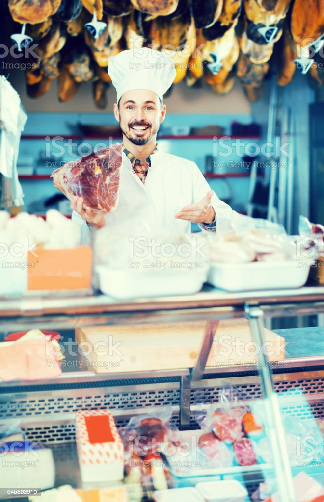 Male shop assistant demonstrating piece of meat in butcher's shop stock photo