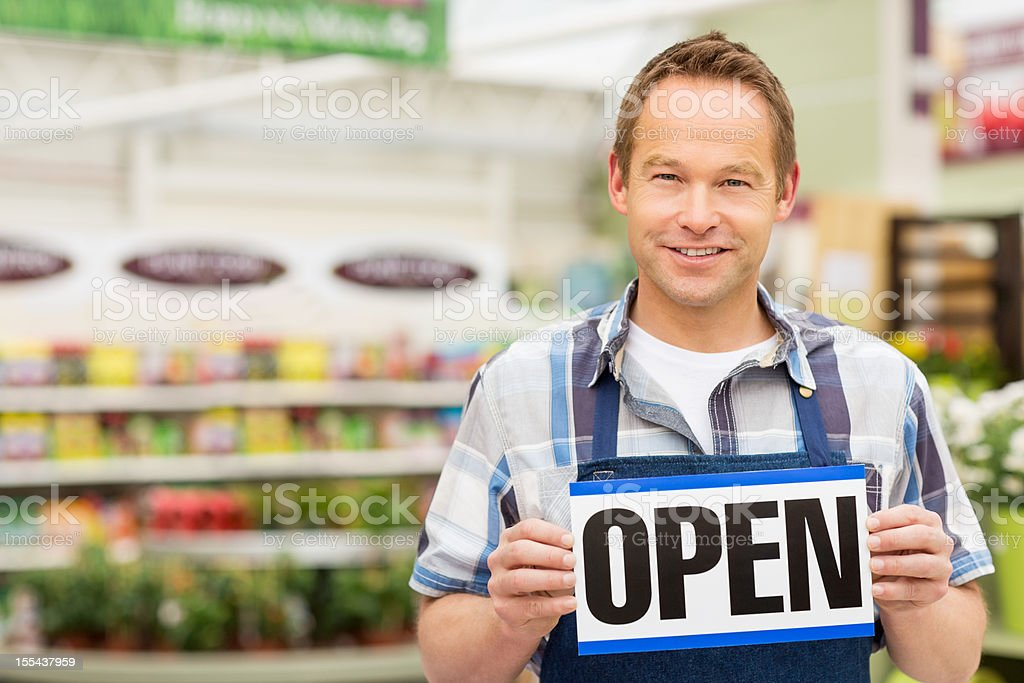Male Shop Owner Holding an Open Signboard royalty-free stock photo