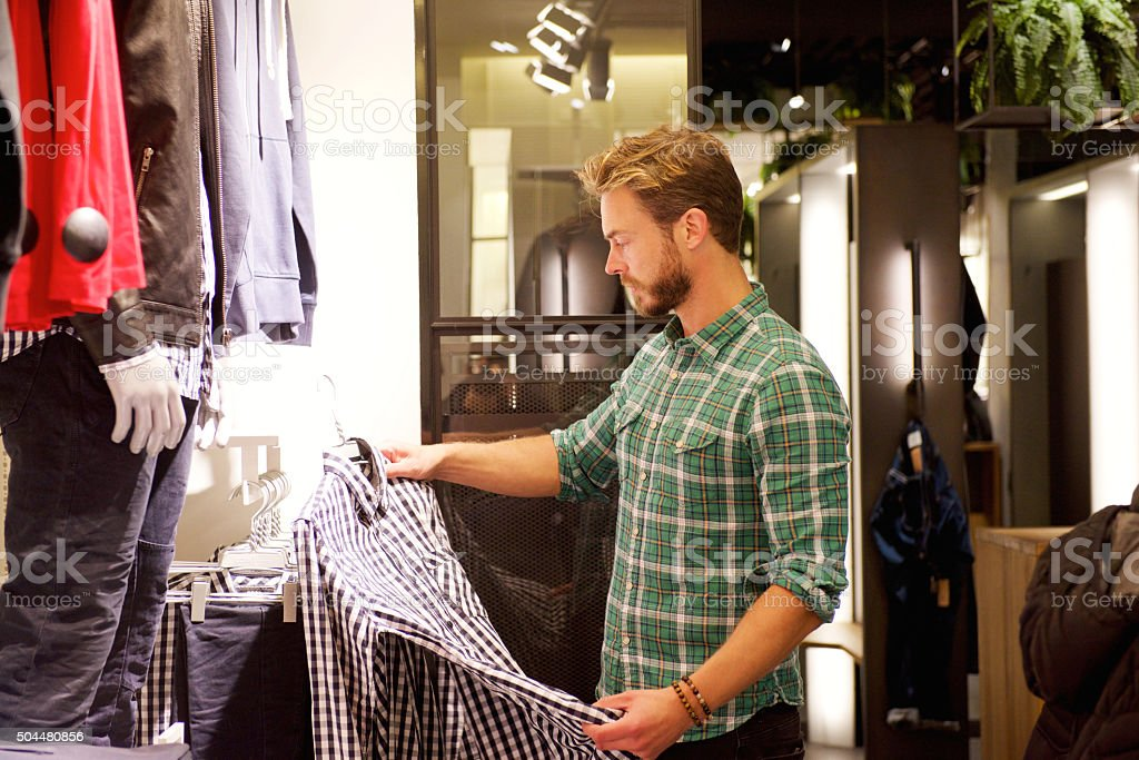 Male shopper looking at clothes in store stock photo