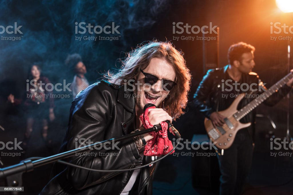 Male singer with microphone and rock and roll band performing hard rock music on stage stock photo