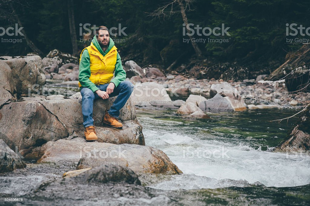 Male sits on a rock near the river in mountains stock photo