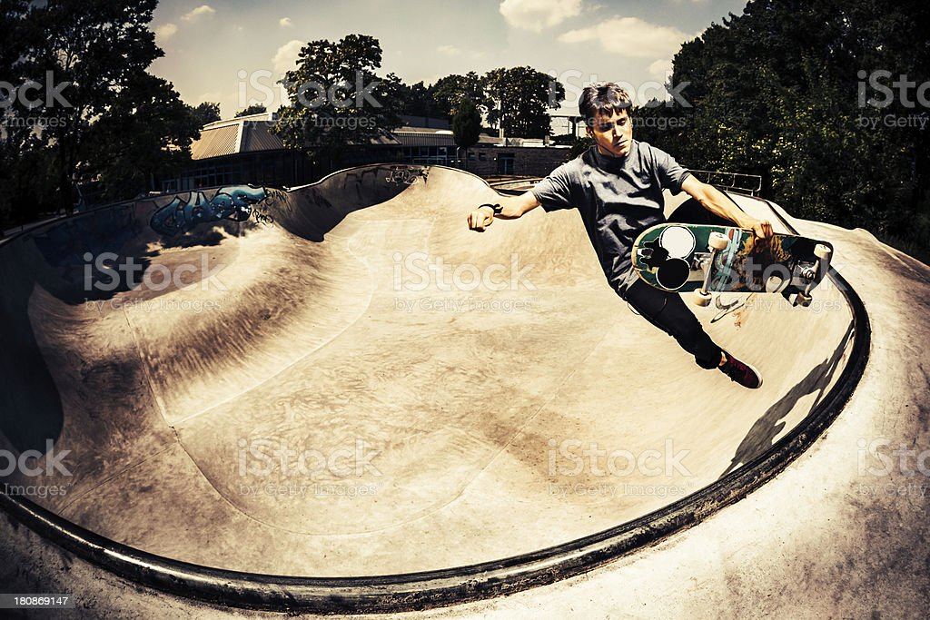 Male skateboarder grabbing his skateboard stock photo