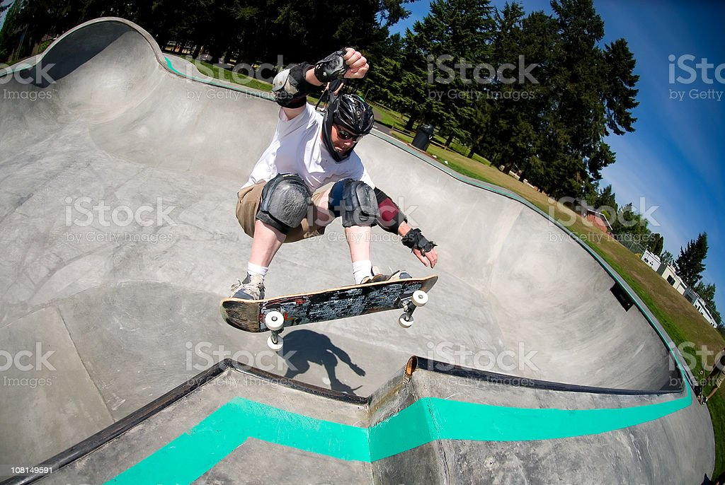 Male Skateboarder in Skate Park on Sunny Day stock photo