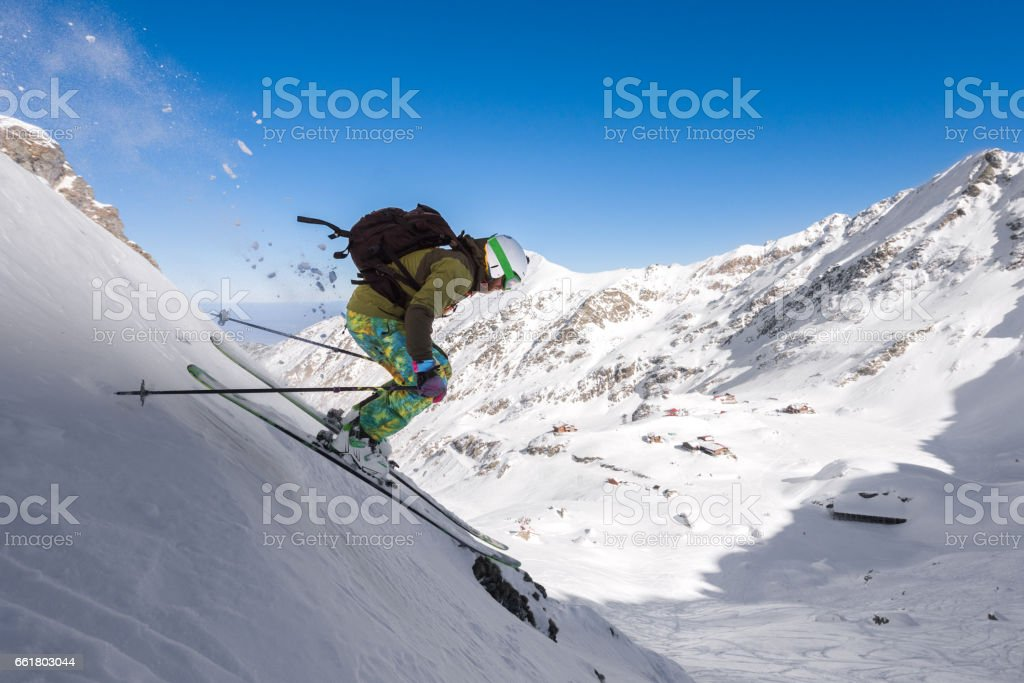 Male skier freeriding downhill a steep slope stock photo