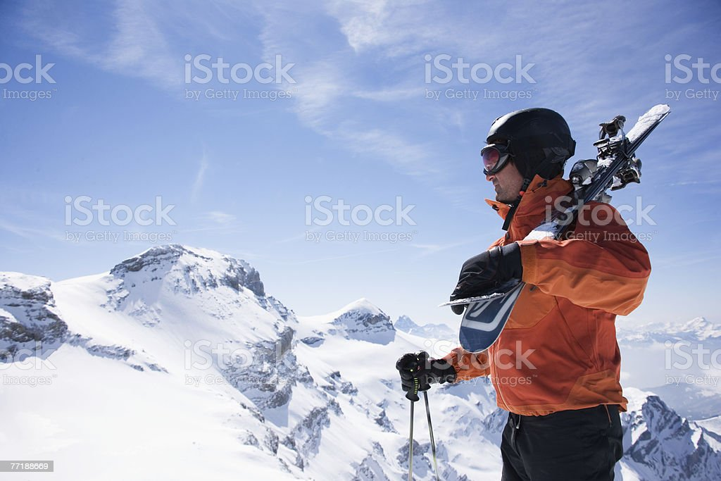 A male skier on a mountain carrying his skis royalty-free stock photo
