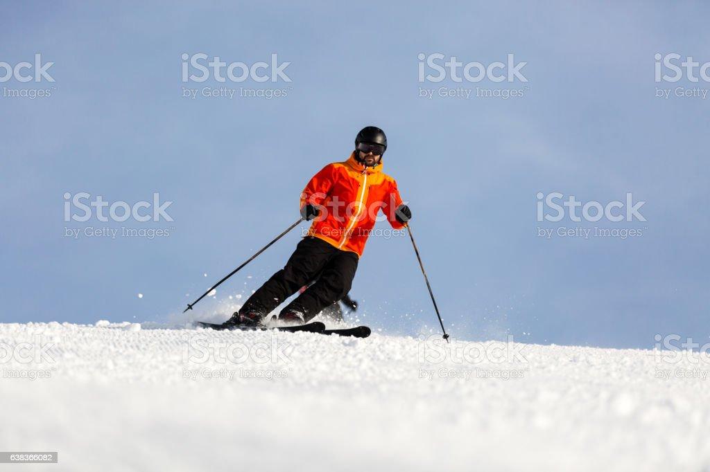 Male skier skiing on ski slope stock photo