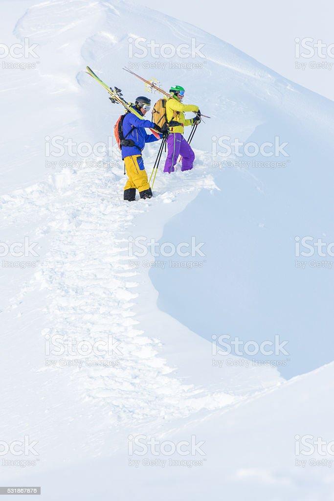 Male skiers walking in snow stock photo