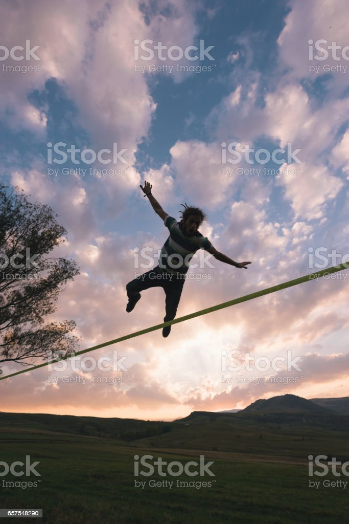 Male slackliner doing extreme tricks outdoor in nature stock photo