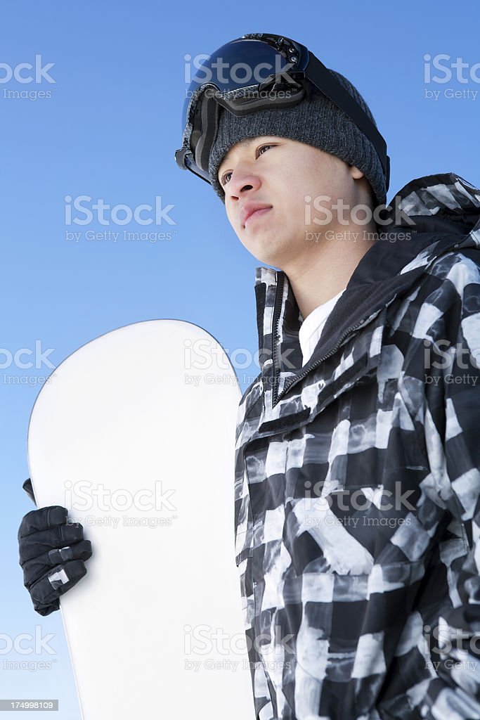 Male snowboarder against blue sky royalty-free stock photo