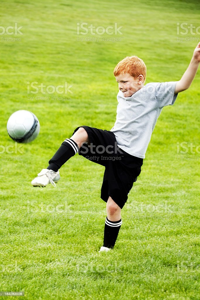 Male Soccer Child Traps Ball in Midair with Foot royalty-free stock photo