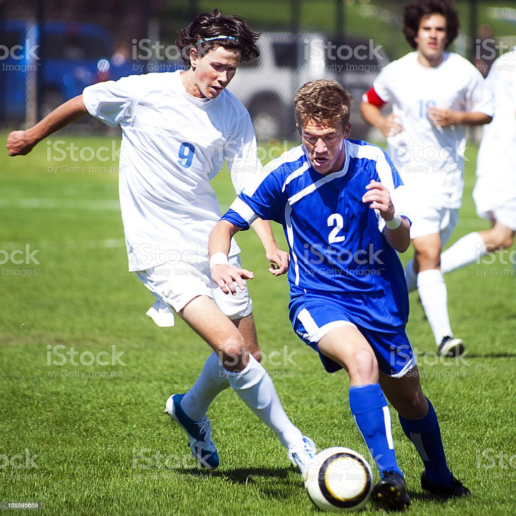 Male Soccer Player Challenges Another Player for Ball from Behind royalty-free stock photo