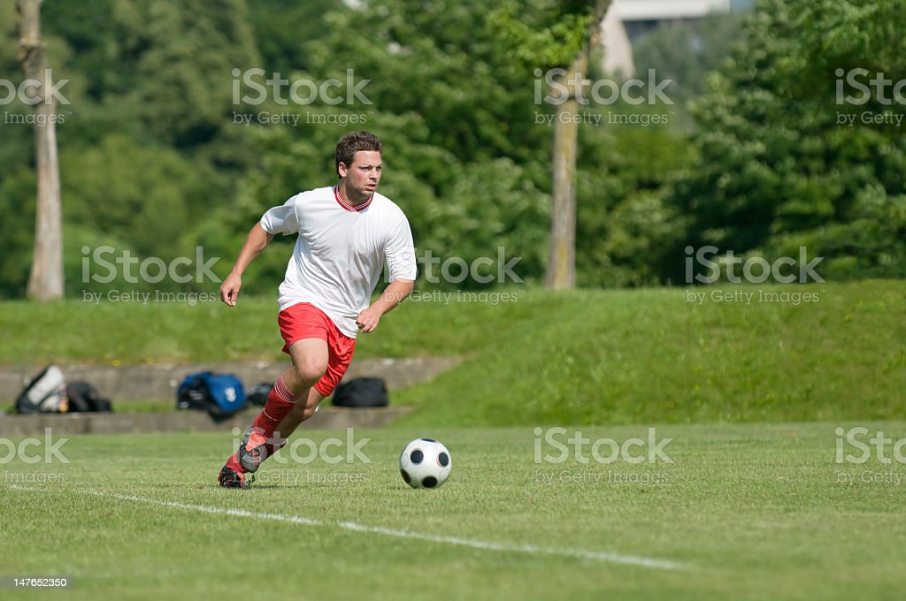 A male soccer player dribbling the ball down the field royalty-free stock photo